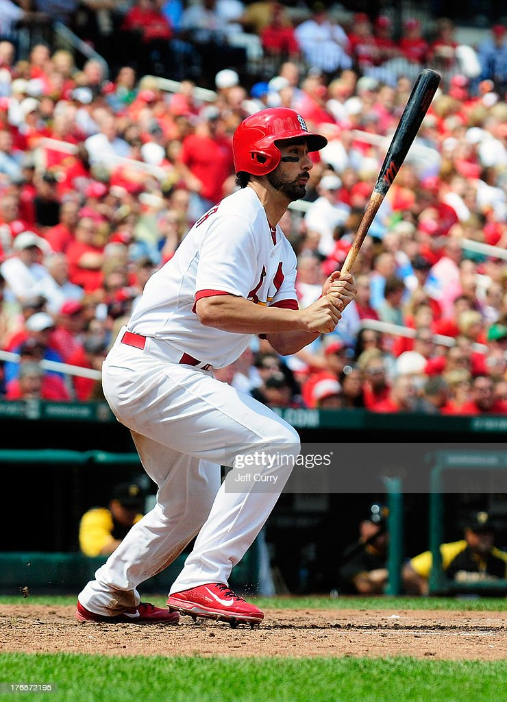 Matt Carpenter #13 of the St. Louis Cardinals hits an RBI triple off of A.J. Burnett (not pictured) of the Pittsburgh Pirates in the fifth inning at Busch Stadium on August 15, 2013 in St. Louis, Missouri. Cardinals won 6-5 in twelve innings.