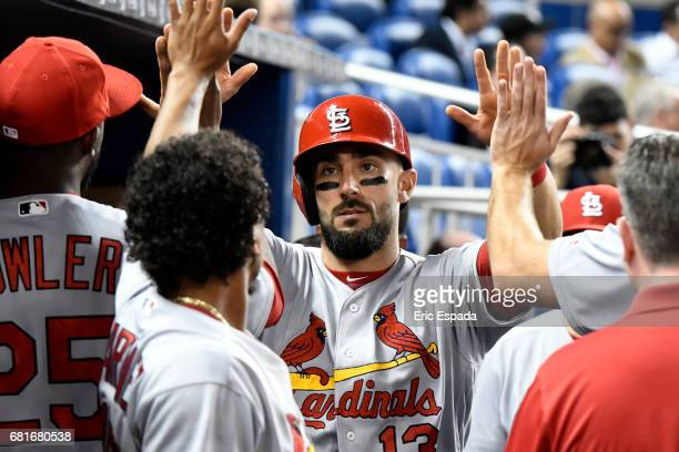 Matt Carpenter of the St Louis Cardinals is congratulated by teammates after scoring in the third inning against the Miami Marlinsat Marlins Park on...