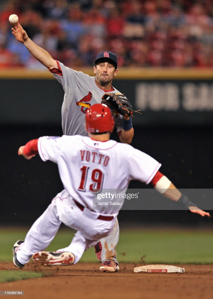 Matt Carpenter of the St Louis Cardinals makes the throw to complete a double play on Joey Votto of the Cincinnati Reds to end the seventh inning at...