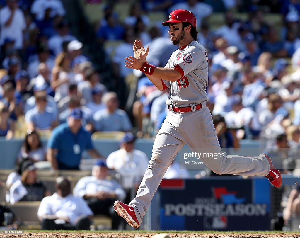 Matt Carpenter #13 of the St. Louis Cardinals reacts as he scores a run in the third inning against the Los Angeles Dodgers in Game Five of the National League Championship Series at Dodger Stadium on October 16, 2013 in Los Angeles, California.