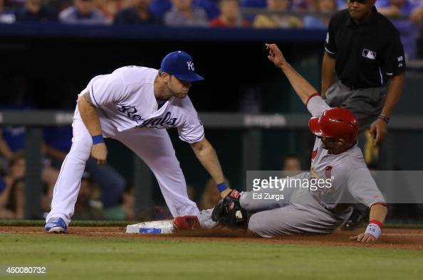Matt Carpenter of the St Louis Cardinals slides into third base safely past the tag of Mike Moustakas of the Kansas City Royals on a Randal Grichuk...