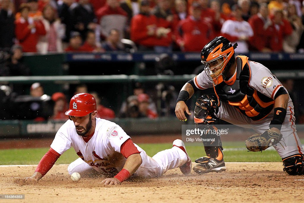Matt Carpenter #13 of the St. Louis Cardinals slides past the plate as he is safe as catcher Hector Sanchez #29 of the San Francisco Giants dropped the ball in the fifth inning in Game Four of the National League Championship Series at Busch Stadium on October 18, 2012 in St Louis, Missouri.