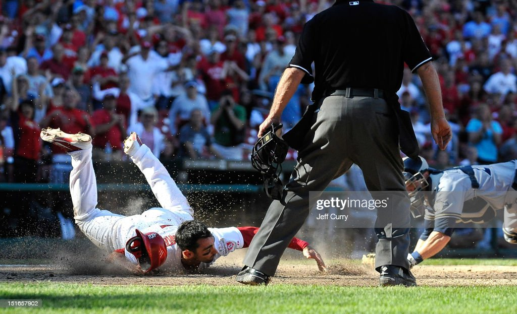 Matt Carpenter #13 of the St. Louis Cardinals slides safely past <a gi-track='captionPersonalityLinkClicked' href=/galleries/search?phrase=Jonathan+Lucroy&family=editorial&specificpeople=5732413 ng-click='$event.stopPropagation()'>Jonathan Lucroy</a> #20 of the Milwaukee Brewers to score the game winning run on a single by <a gi-track='captionPersonalityLinkClicked' href=/galleries/search?phrase=Allen+Craig&family=editorial&specificpeople=4405049 ng-click='$event.stopPropagation()'>Allen Craig</a> #21 in the 10th inning at Busch Stadium on September 9, 2012 in St. Louis, Missouri. The Cardinals won 5-4.