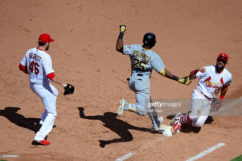 Matt Carpenter #13 of the St. Louis Cardinals slides to force out Gregory Polanco #25 of the Pittsburgh Pirates to end the eighth inning at Busch Stadium on April 19, 2017 in St Louis, Missouri.