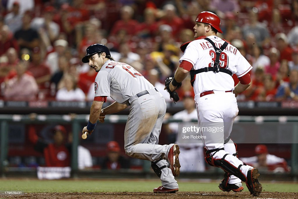 Matt Carpenter #13 of the St. Louis Cardinals tries to avoid being tagged by <a gi-track='captionPersonalityLinkClicked' href=/galleries/search?phrase=Devin+Mesoraco&family=editorial&specificpeople=5745587 ng-click='$event.stopPropagation()'>Devin Mesoraco</a> #39 of the Cincinnati Reds after striking out during the game at Great American Ball Park on September 4, 2013 in Cincinnati, Ohio. The Cardinals won 5-4 in 16 innings.