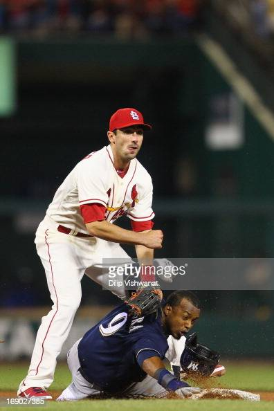 Matt Carpenter of the St Louis Cardinals turns a double play against Jean Segura of the Milwaukee Brewers in the eighth inning at Busch Stadium on...
