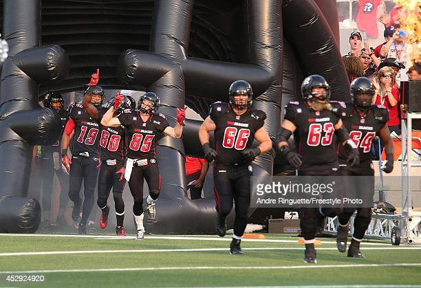 Matt Carter Nolan MacMillan Jon Gott and J'Micheal Deane of the Ottawa Redblacks run out of the players' tunnel prior to their home opener against...