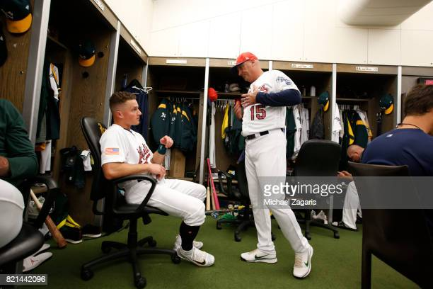 Matt Chapman and Acting Third Base Coach Steve Scarsone of the Oakland Athletics go over signs in the clubhouse prior to the game against the Chicago...