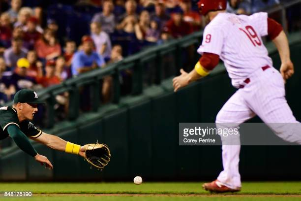 Matt Chapman of the Oakland Athletics can't get to a diving ground ball as Tommy Joseph of the Philadelphia Phillies looks on advancing to third base...