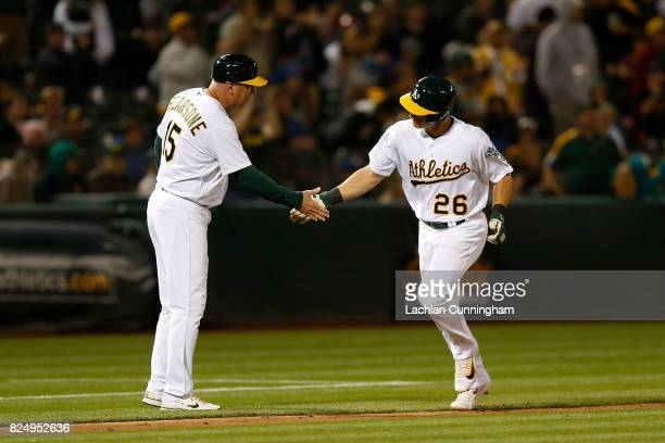Matt Chapman of the Oakland Athletics celebrates with third base coach Steve Scarsone after hitting a solo home run in the eighth inning against the...