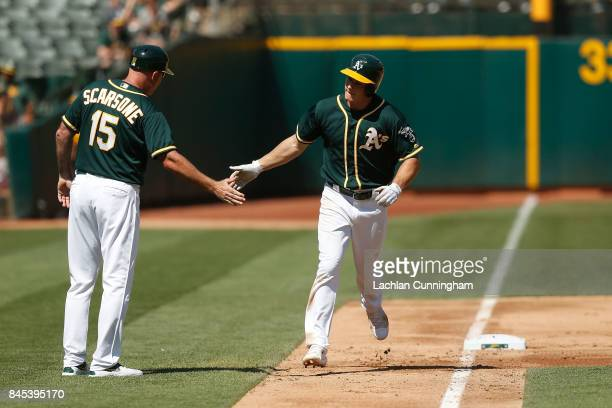 Matt Chapman of the Oakland Athletics celebrates with third base coach Steve Scarsone after hitting a solo home run in the fifth inning against the...