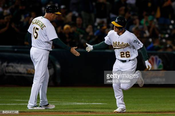 Matt Chapman of the Oakland Athletics is congratulated by acting third base coach Steve Scarsone after hitting a two run home run against the Houston...