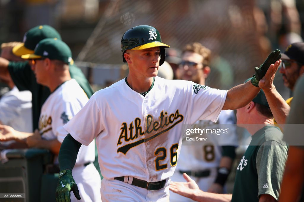 Matt Chapman #26 of the Oakland Athletics is congratulated by teammates after he hit a two-run home run in the eighth inning against the Kansas City Royals at Oakland Alameda Coliseum on August 16, 2017 in Oakland, California.
