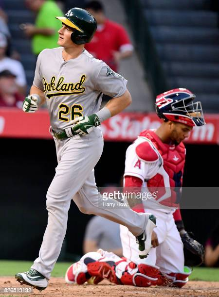 Matt Chapman of the Oakland Athletics scores in front of Martin Maldonado of the Los Angeles Angels after his three run homerun to take a 30 lead...