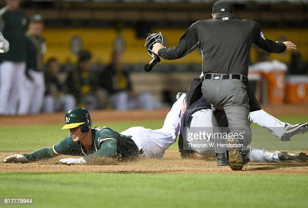 Matt Chapman of the Oakland Athletics slides by the tag scoring on a wild pitch by Nick Goody of the Cleveland Indians in the bottom of the seventh...