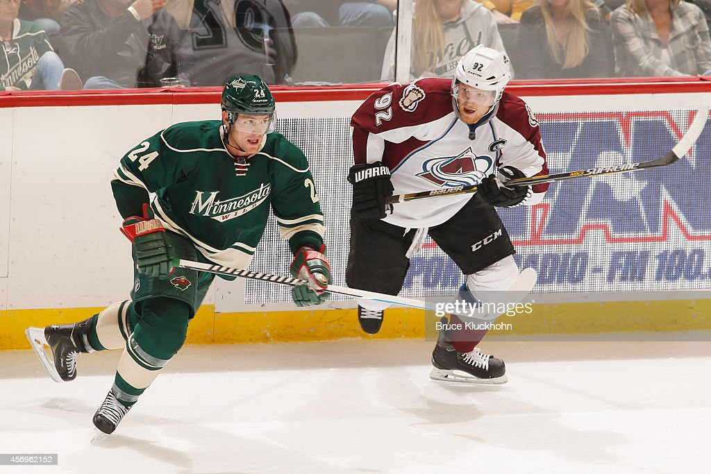 Matt Cooke of the Minnesota Wild and Gabriel Landeskog of the Colorado Avalanche skate to the puck during the season opener on October 9 2014 at the...