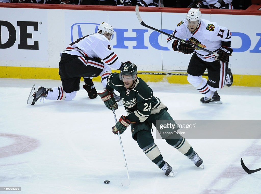 Matt Cooke of the Minnesota Wild controls the puck as Nick Leddy and Jeremy Morin of the Chicago Blackhawks look on during the first period in Game...