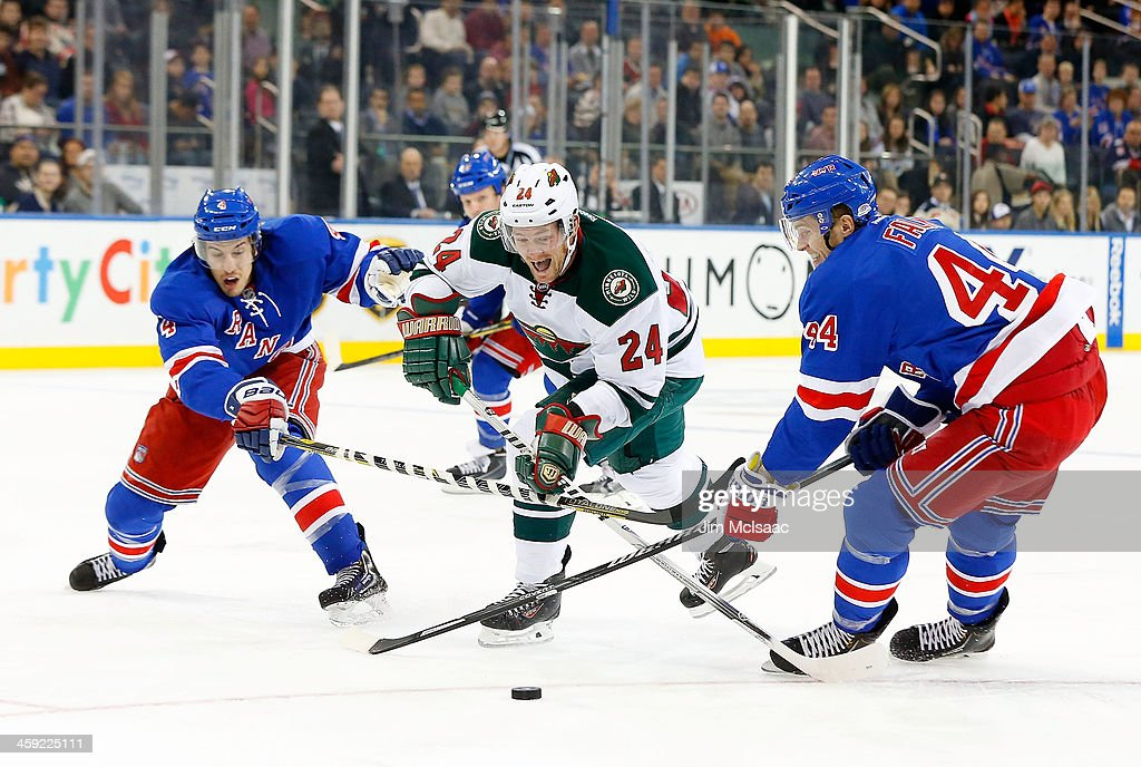 <a gi-track='captionPersonalityLinkClicked' href=/galleries/search?phrase=Matt+Cooke&family=editorial&specificpeople=592551 ng-click='$event.stopPropagation()'>Matt Cooke</a> #24 of the Minnesota Wild tries to split the defense of <a gi-track='captionPersonalityLinkClicked' href=/galleries/search?phrase=Michael+Del+Zotto&family=editorial&specificpeople=4044191 ng-click='$event.stopPropagation()'>Michael Del Zotto</a> #4 and <a gi-track='captionPersonalityLinkClicked' href=/galleries/search?phrase=Justin+Falk&family=editorial&specificpeople=4324950 ng-click='$event.stopPropagation()'>Justin Falk</a> #44 of the New York Rangers during the first period at Madison Square Garden on December 22, 2013 in New York City.