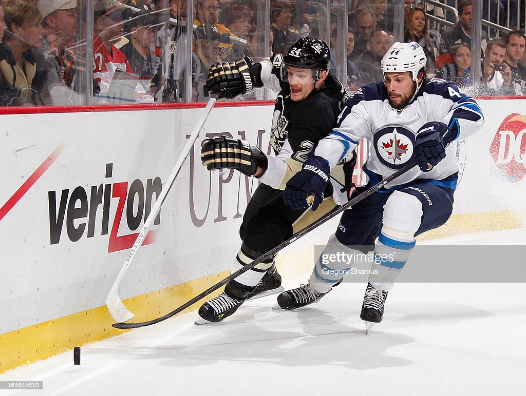 Matt Cooke #24 of the Pittsburgh Penguins battles for the puck against Zach Bogosian #44 of the Winnipeg Jets on March 28, 2013 at Consol Energy Center in Pittsburgh, Pennsylvania.