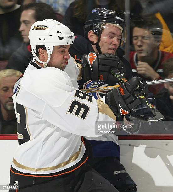 Matt Cooke of the Vancouver Canuck is checked into the boards by Travis Green of the Anaheim Ducks at General Motors Place November 30 2006 in...