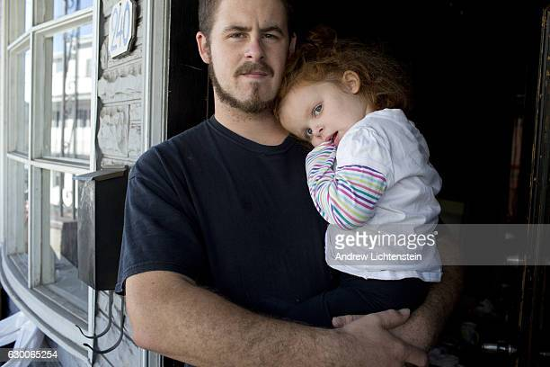 Matt Coop a Trump supporter stands in his doorway with his child in the economically depressed town of Shenandoah Pennsylvania one day before the...