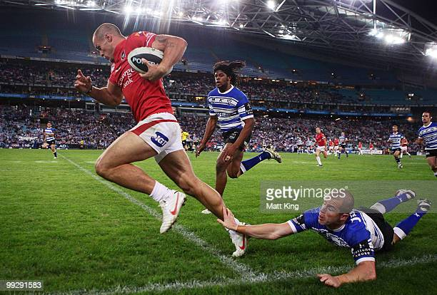 Matt Cooper of the Dragons beats the tackle of Luke Patten of the Bulldogs to score a try during the round 10 NRL match between the...