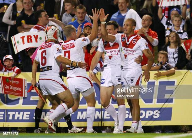 Matt Cooper of the Dragons celebrates with team mates after scoring during the round eight NRL match between the St George Dragons and the Cronulla...