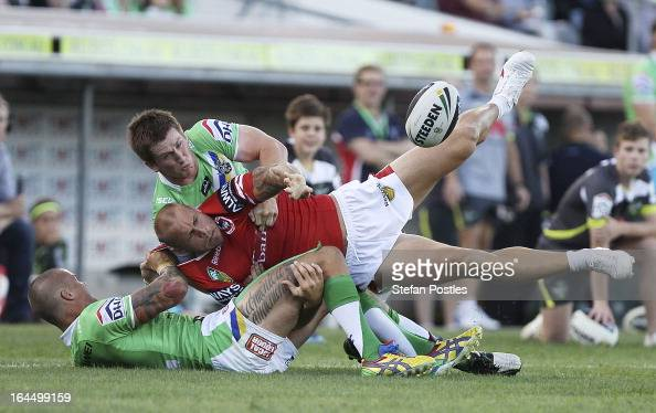 Matt Cooper of the Dragons gets dragged towards the sideline during the round three NRL match between the Canberra Raiders and the St George...