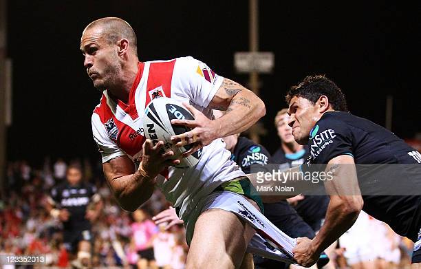 Matt Cooper of the Dragons is tackled by Brad Tighe of the Panthers during the round 26 NRL match between the St George Illawarra Dragons and the...