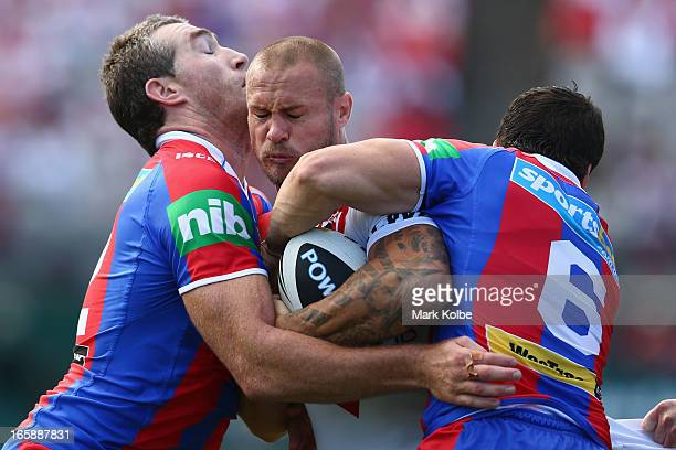 Matt Cooper of the Dragons is tackled during the round five NRL match between the St George Illawarra Dragons and the Newcastle Knights at WIN...