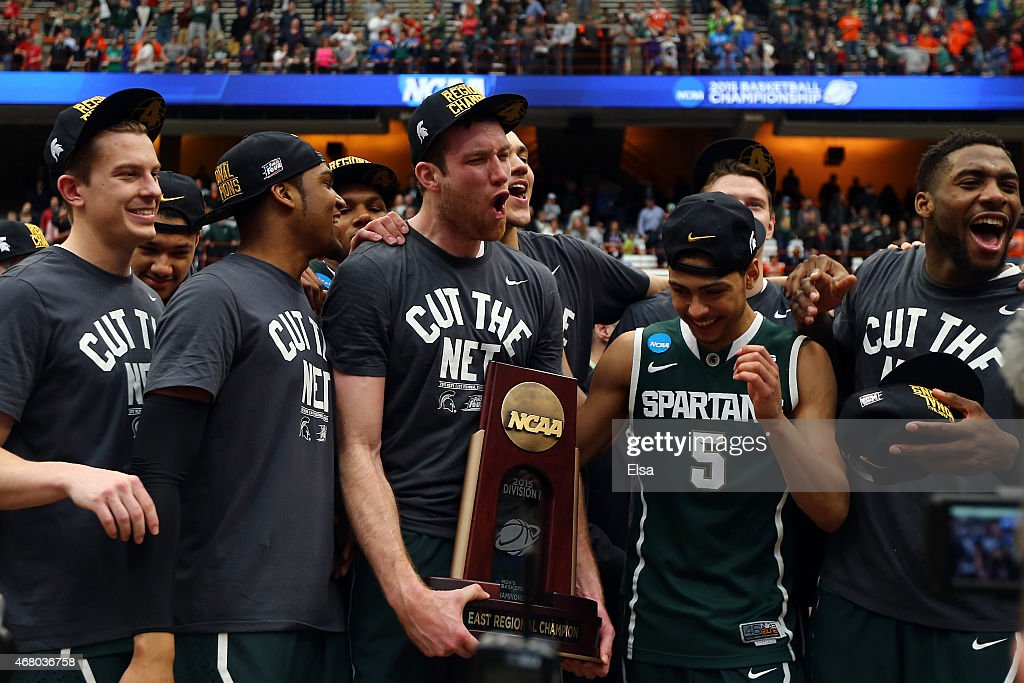 Matt Costello of the Michigan State Spartans celebrate with the trophy after defeating the Louisville Cardinals 76 to 70 in overtime of the East...
