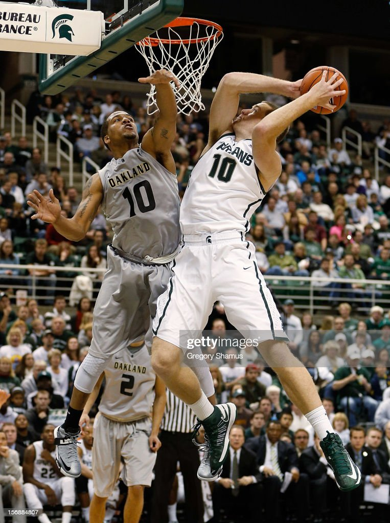 Matt Costello #10 of the Michigan State Spartans gets a second half shot off around the defense of Duke Mondy #10 of the Oakland Golden Grizzlies at the Jack T. Breslin Students Events Center on November 23, 2012 in East Lansing, Michigan. Michigan State won the game 70-52.