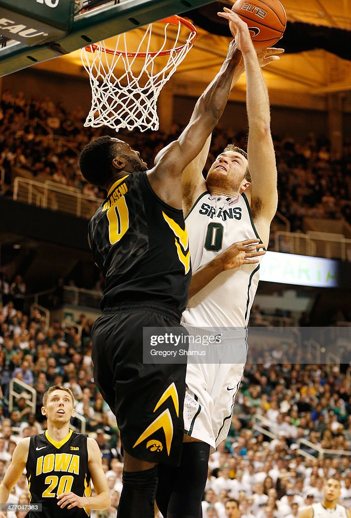 Matt Costello #10 of the Michigan State Spartans tries to dunk over Gabriel Olaseni #00 of the Iowa Hawkeyes during the second half at the Jack T. Breslin Student Events Center on February 6, 2014 in East Lansing, Michigan.