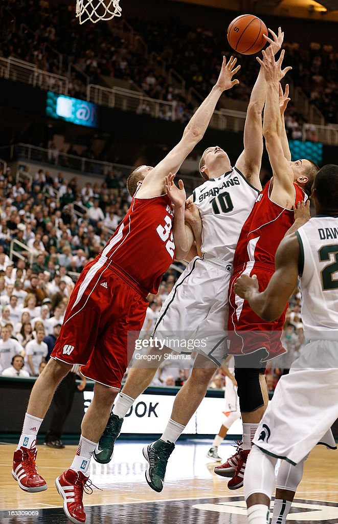 Matt Costello #10 of the Michigan State Spartans tries to grab a first half rebound between Evan Anderson #32 and Ben Brust #1 of the Wisconsin Badgers at the Jack T. Breslin Student Events Center on March 7, 2013 in East Lansing, Michigan.