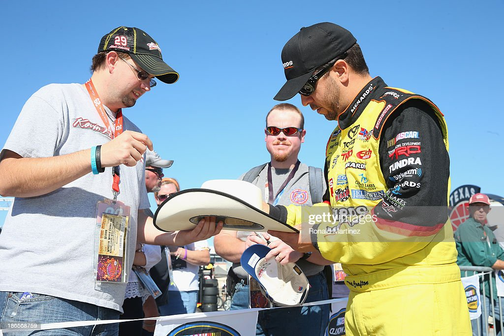 Matt Crafton, driver of the #88 Fisher Nuts / Menards Toyota, signs autographs for fans during qualifying for the NASCAR Camping World Truck Series WinStar World Casino 350k at Texas Motor Speedway on November 1, 2013 in Fort Worth, Texas.