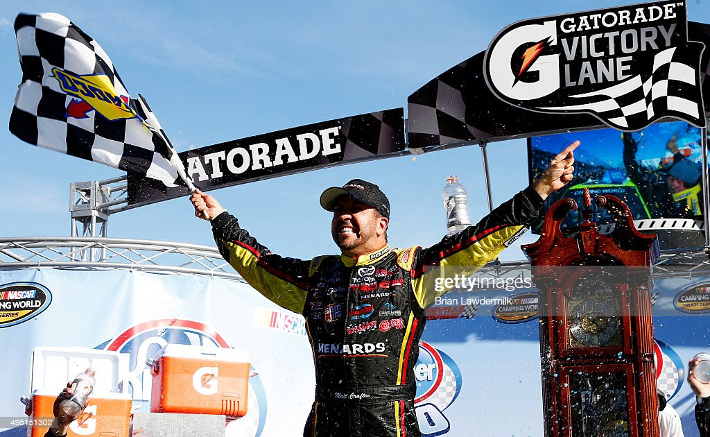 Matt Crafton driver of the Fisher Nuts/Menards Toyota celebrates in victory lane after winning the NASCAR Camping World Truck Series Kroger 200 at...
