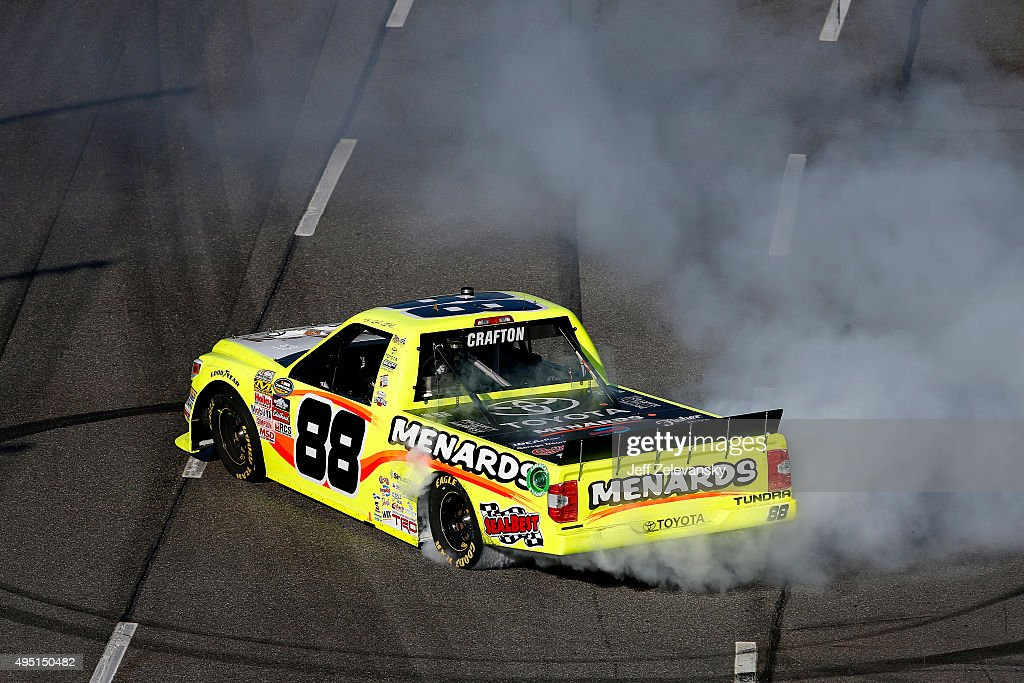 Matt Crafton driver of the Fisher Nuts/Menards Toyota celebrates with a burnout after winning the NASCAR Camping World Truck Series Kroger 200 at...
