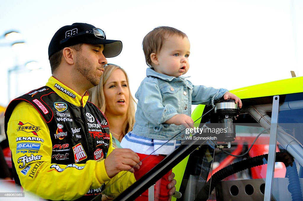 Matt Crafton, driver of the #88 Goof Off/Mendards Toyota, and his wife, Ashley, stand on the grid with their daughter, Elladee Ann, during the NASCAR Camping World Truck Series SFP 250 at Kansas Speedway on May 9, 2014 in Kansas City, Kansas.