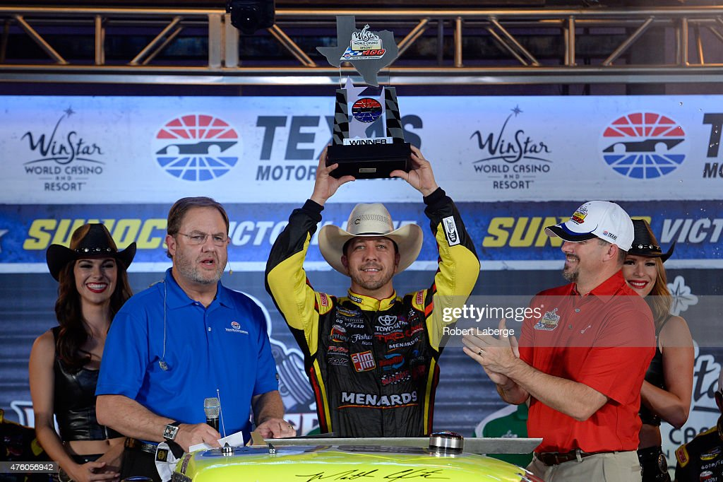 Matt Crafton driver of the Ideal Door/Menards Toyota celebrates with the trophy after winning the NASCAR Camping World Truck Series WinStar World...