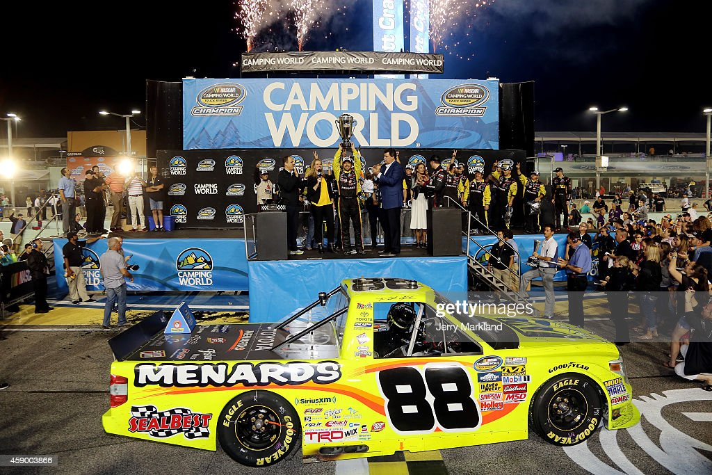 Matt Crafton driver of the JeldWen/Menards Toyota celebrates winning the series championship with the trophy in Victory Lane after the NASCAR Camping...