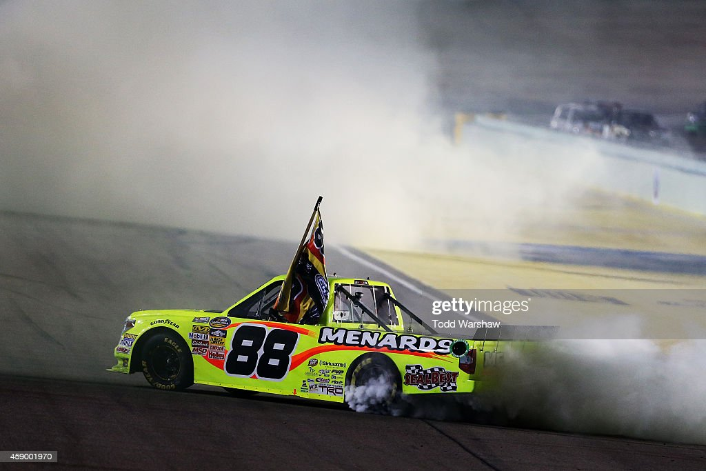 Matt Crafton driver of the JeldWen/Menards Toyota celebrates with a burnout after winning the series championship and placing ninth in the NASCAR...
