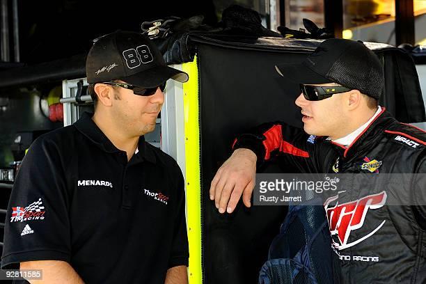Matt Crafton driver of the Menards/McGuireNicholas Chevrolet talks with David Gilliland driver of the Menards Chevrolet in the garage area during...