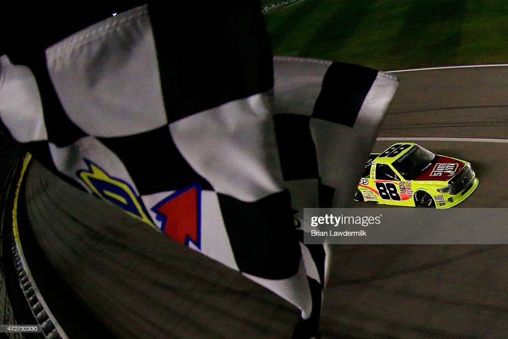 Matt Crafton driver of the Slim Jim/Menards Toyota takes the checkered flag to win the NASCAR Camping World Truck Series Toyota Tundra 250 at Kansas...