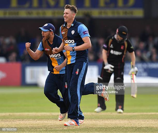 Matt Critchley of Derbyshire Falcons is congratulated by Alex Hughes on taking the wicket of Ben Raine of Leicestershire Foxes during the NatWest T20...