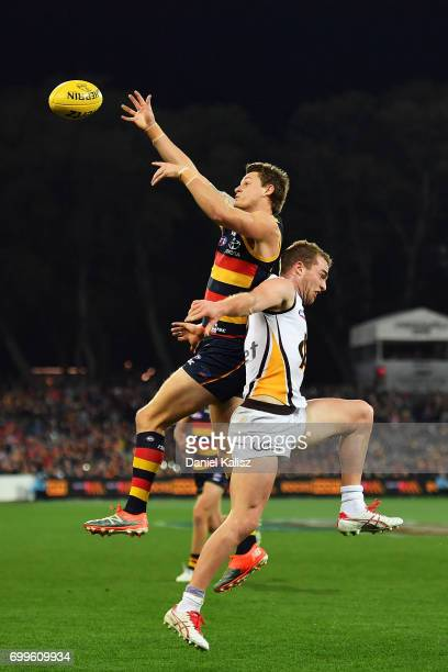 Matt Crouch of the Crows and Tom Mitchell of the Hawks compete for the ball during the round 14 AFL match between the Adelaide Crows and the Hawthorn...