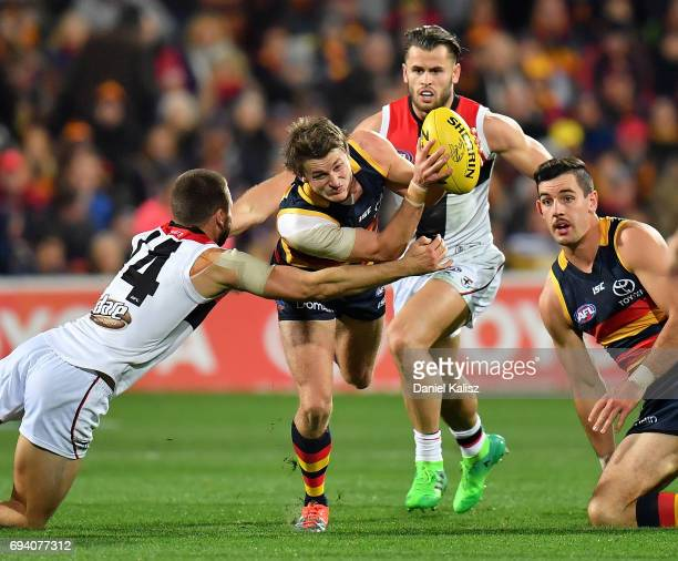 Matt Crouch of the Crows evades a tackle from Jarryn Geary of the Saints during the round 12 AFL match between the Adelaide Crows and the St Kilda...