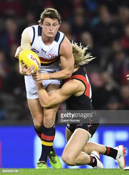 Matt Crouch of the Crows handballs whilst being tackled by Dyson Heppell of the Bombers during the round 21 AFL match between the Essendon Bombers...