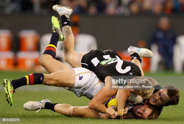 Matt Crouch of the Crows is tackled by Jordan De Goey and Darcy Moore of the Magpies during the 2017 AFL round 19 match between the Collingwood...