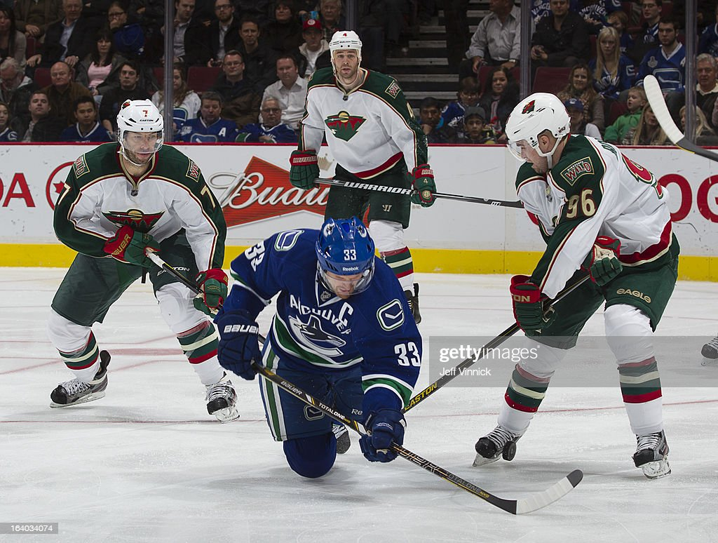 Matt Cullen #7 and Pierre-Marc Bouchard #96 of the Minnesota Wild combine to check Henrik Sedin #33 of the Vancouver Canucks during their NHL game at Rogers Arena March 18, 2013 in Vancouver, British Columbia, Canada. Minnesota won 3-1.