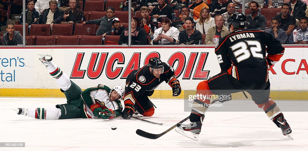 Matt Cullen #7 of the Minnesota Wild and Francois Beauchemin #23 of the Anaheim Ducks battle for the puck as the Toni Lydman #32 of the Anaheim Ducks approaches during the game on March 1, 2013 at Honda Center in Anaheim, California.